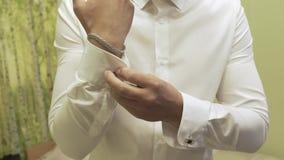 O homem bem sucedido no terno azul endireita suas luvas, close-up vídeos de arquivo
