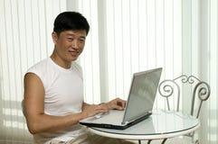 O homem bem sucedido novo com o computador Fotografia de Stock Royalty Free