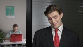 O homem bem sucedido novo em um terno mostra o desprezo, desconfiança, emoção da desconfiança O homem trabalha em um computador n vídeos de arquivo