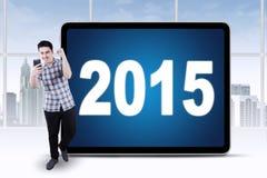 O homem bem sucedido obtém uma boa notícia com números 2015 Fotos de Stock
