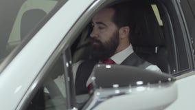 O homem bem sucedido que senta-se no compartimento de passageiro do veículo novo inspeciona o interior do automóvel recentemente  filme