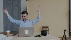 O homem bem sucedido seguro comemora vitórias Dança feliz nova do freelancer em seu local de trabalho Mãos de ondulação do venced video estoque