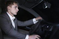 O homem bem vestido novo em um terno está sentando-se em seu carro antes de ir em uma noite para fora no Pequim foto de stock