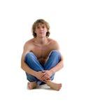 O homem bonito senta-se no assoalho Imagem de Stock