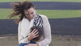 O homem bonito torce sua menina bonita nas mãos na natureza lentamente vídeos de arquivo