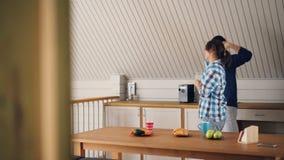 O homem brincalhão e a mulher dos pares novos adoráveis são de dança e de riso na cozinha em casa que apreciam o tempo livre e o  filme
