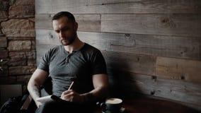 O homem brutal com restolho e com braços tattooed está situando no café e toma notas