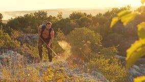 O homem brutal que bate a pedra com o martelo na rocha lentamente filme