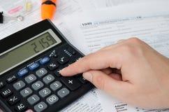 O homem calcula o imposto de renda imagens de stock