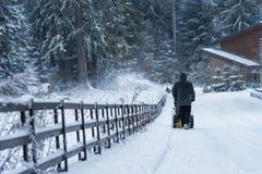 O homem cancela a neve com o snowblower após a queda de neve do inverno foto de stock royalty free