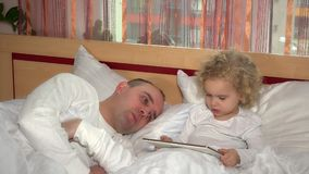 O homem cansado do pai cair adormecido quando filha da criança que olha no tablet pc vídeos de arquivo