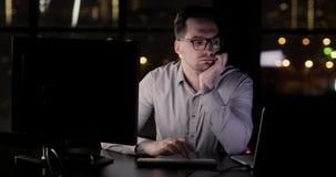 O homem cansado do programador está trabalhando no escritório que datilografa fora do tempo estipulado no teclado tarde na noite video estoque