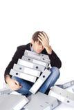 O homem cansado está sentando-se com muitos dobradores de papel isolados em b branco Imagens de Stock