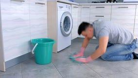 O homem cansado infeliz nas luvas de borracha lava e fricciona duramente o assoalho na cozinha Vista lateral video estoque