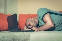 O homem cansado novo que toma uma ruptura e caiu adormecido na cama com seu computador da parte superior do regaço após duramente fotografia de stock