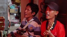 O homem canta no mercado do alimento em Jakarta, Indonésia filme