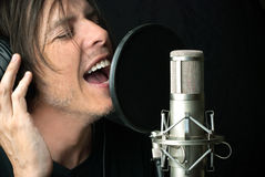 O homem canta no microfone de condensador Fotografia de Stock