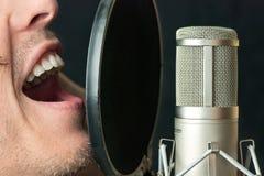 O homem canta no microfone de condensador, fim Fotografia de Stock Royalty Free