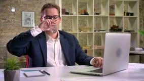 O homem caucasiano à moda bonito é focalizado em seu trabalho e na datilografia no portátil, descansando pela água potável no esc vídeos de arquivo
