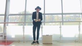 O homem caucasiano à moda em um chapéu e os dólares pretos do dinheiro das contagens do terno no banco, ao lado dele são uma mala filme