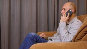 O homem caucasiano adulto faz a chamada com smartphone O homem branco senta-se na poltrona em casa Homem da vista lateral que fal filme