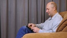 O homem caucasiano adulto olha a foto na tabuleta O homem branco senta-se na poltrona e na tabuleta do uso video estoque
