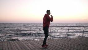 O homem caucasiano aquece-se durante um exercício do amanhecer contratado no encaixotamento O desportista masculino no sportswear vídeos de arquivo