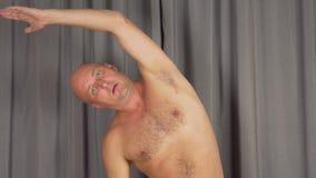O homem caucasiano branco adulto que estica suas vértebras e aquece o corpo O homem exercita na sala de visitas video estoque