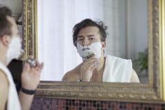 O homem caucasiano considerável novo começa a barbear com escova e espuma, estilo do vintage do barbeiro idoso Olhar sério pensat fotografia de stock