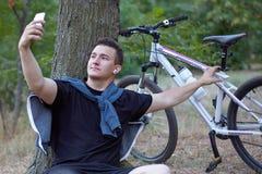 O homem caucasiano considerável novo faz o selfie no telefone celular, sentando-se na terra perto da árvore grande no parque aban imagem de stock