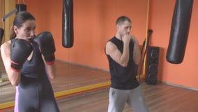 O homem caucasiano do instrutor ensina as artes marciais da menina que praticam uma greve, autodefesa no gym, movimento lento vídeos de arquivo