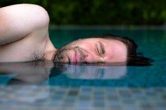O homem caucasiano está receoso nadar na piscina Não gosta da água de cloro e não fecha seus olhos imagens de stock royalty free