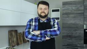 O homem caucasiano farpado gordo como um cozinheiro que veste um avental está em uma cozinha e em olhares na câmera video estoque
