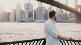 O homem caucasiano feliz está a cerca próxima da terraplenagem do rio no cenário da ponte de Brooklyn, refletindo e apreciando a  filme