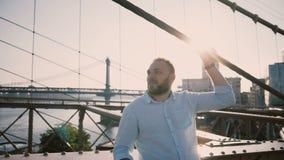 O homem caucasiano feliz novo está de sorriso na ponte de Brooklyn, as cruzes armam-se e olham-se em torno de apreciar a vista 4K vídeos de arquivo