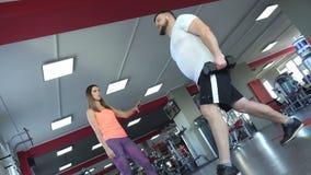 O homem caucasiano gordo com uma barba no gym executa ocupas de um exercício com os pesos sob a supervisão da vídeos de arquivo