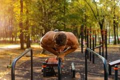 O homem caucasiano novo atlético que faz o impulso levanta em barras paralelas foto de stock royalty free