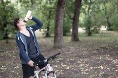 O homem caucasiano novo bebe a água que bicycling no parque fotos de stock