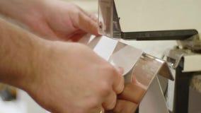 O homem caucasiano prende folhas do folheto com grampeador bonde filme