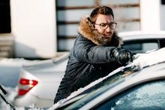 O homem caucasiano que veste o revestimento morno remove a neve do veículo, limpando após o blizzard da neve fotografia de stock