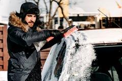 O homem caucasiano remove a neve do veículo, limpando a neve após o blizzard fotos de stock royalty free