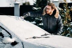 O homem caucasiano remove a neve do veículo, limpando a neve após o blizzard imagem de stock
