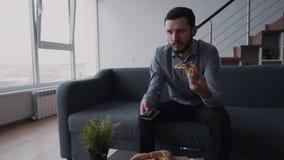 O homem caucasiano sério no vestuário formal está sentando-se no sofá e na tevê de observação vídeos de arquivo