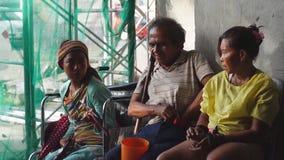 O homem cego ao lado do mendigo deficiente no portal da igreja é lugares encontrados das cenas familiares em público vídeos de arquivo