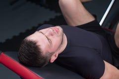 O homem centrou-se sobre os pés do treinamento na máquina no gym Fotografia de Stock Royalty Free