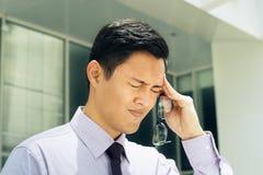 O homem chinês com monóculos sofre a miopia e a dor de cabeça Foto de Stock Royalty Free