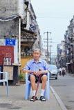 O homem chinês de Elderley senta-se em uma cadeira plástica fora, Xiang Yang, China Fotos de Stock