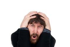 O homem choc com uma barba prende a cabeça das mãos Imagem de Stock