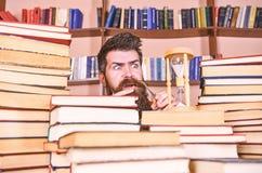 O homem, cientista olha a ampulheta Conceito de fluxo do tempo Professor ou estudante com barba que estudam na biblioteca Homem e fotografia de stock