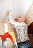 O homem cola a telha do teto na cozinha imagens de stock